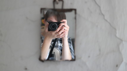 A photographer is taking a picture of her own in the mirror hanging on the white old wall