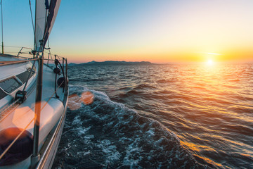 Wall Mural - Luxury sailing ship yacht boat in the Aegean Sea during beautiful sunset.
