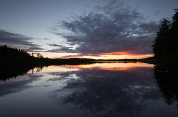 Beautiful sunsetting over a calm lake in sweden after a summers day