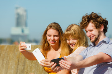 Friends taking selfie photo with smartphone.