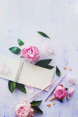 Minimal styled flat lay with peony flowers, petals and blank notebook on a white background