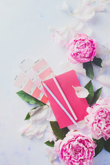 Minimal styled flat lay with peony flowers, petals, stationery and blank notebook on a pastel background