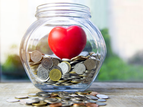 Concept pay attention in saving. Red heart in glass jar with coins.