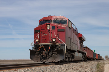 Big Red Locomotive Leading Freight Train on Prairie