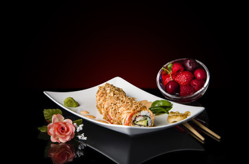 japanese sushi rolls on black glossy surface with strawberry and sushi flower decoration