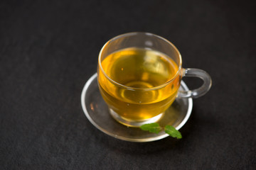 Black tea in a glass cup and tea leaves on black stone background.