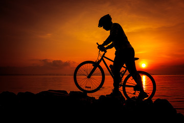 Silhouette of bicyclist enjoying the view at seaside. Outdoors.