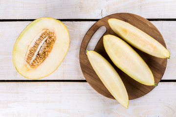 Three slices of fresh melon on the wooden kitchen board