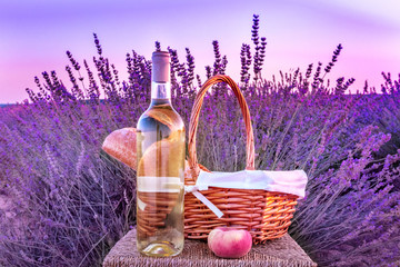 Aluminium Prints Picnic Bottle of white wine and picnic basket in lavender field