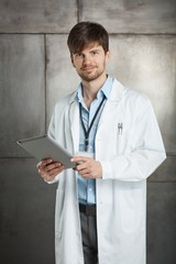 Young doctor holding tablet