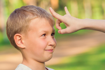 Blond boy waiting for a flick of finger in the forehead