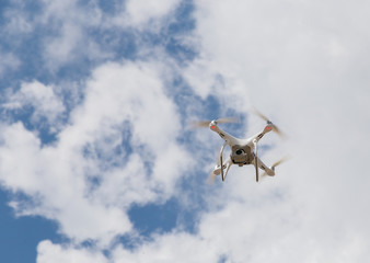 Drone quad copter against a background of blue sky and clouds