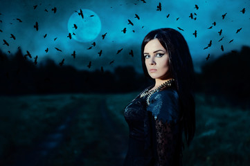 A young witch on background of a full moon and a flock of crows. Portrait of a attractive woman in a black dress in a low key. Fantasy illustration. Fairy tale