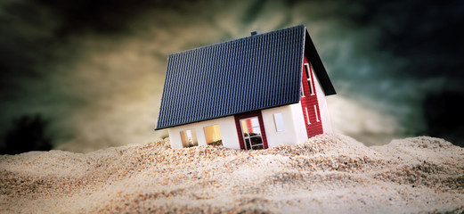 Miniature of house standing in sand