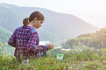 Cute teenager girl drawing with watercolor outdoors sitting on green grass in beautiful place among the mountains in the rays of the setting sun