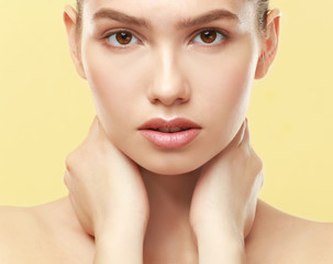 Closeup view of beautiful young woman with natural lips makeup touching neck on color background
