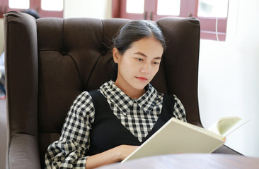 Young asian woman reading book in the library.