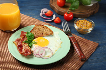Delicious over easy egg with toast and bacon on kitchen table