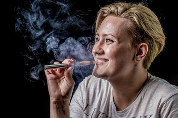 Happy woman smoking electronic cigarette