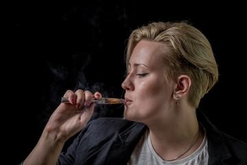Woman sucking smoke from electronic cigarette