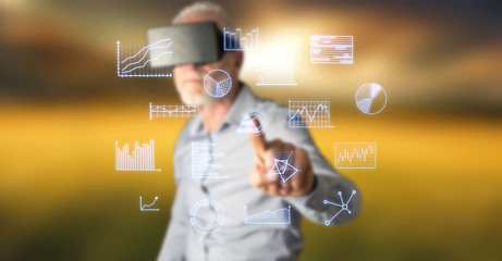 Man wearing a reality virtual headset touching business charts on a touch screen