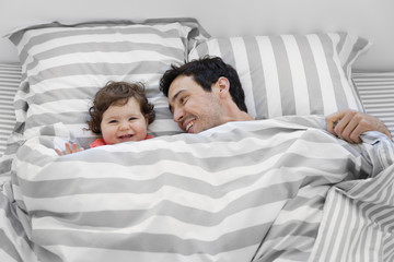 Smiling man and baby girl lying in bed under stripy duvet.