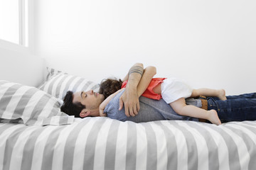 Man wearing grey T-shirt and jeans lying on bed with stripy duvet, hugging baby girl in red dress.