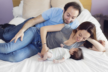 Man, woman and newborn baby girl lying on a bed.