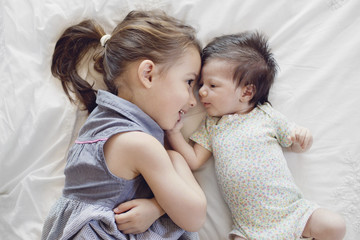 Girl with ponytail and newborn baby girl lying on bed