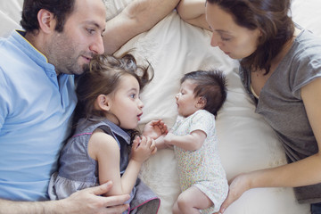 High angle view of man, woman, young girl and newborn baby girl lying on a bed.