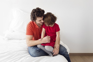 man with brown hair wearing jeans and red T-shirt sitting on a bed, hugging a girl in a red dress.