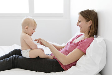Smiling woman sitting on a bed, playing with a baby boy sitting on her lap/