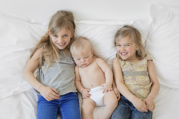 High angle view of two blond girls and baby boy wearing nappy lying side by side on a bed.