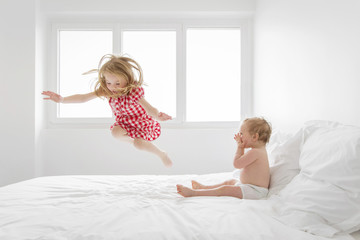 Smiling blond girl wearing red and white checked dress jumping on bed, baby boy sitting next to her, watching.