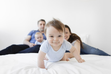 Baby boy crawling on a bed, man, woman and baby boy sitting in the background.