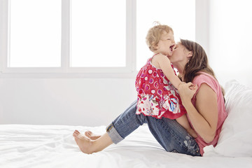 Woman sitting on bed, hugging young girl