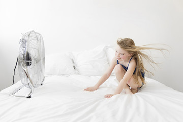 A child, a girl seated on a bed in front of a moving cooling fan with a metal cover with her hair blowing in the moving air.