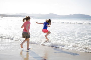 Two girls wearing shorts playing on a sandy beach, jumping into a wave.