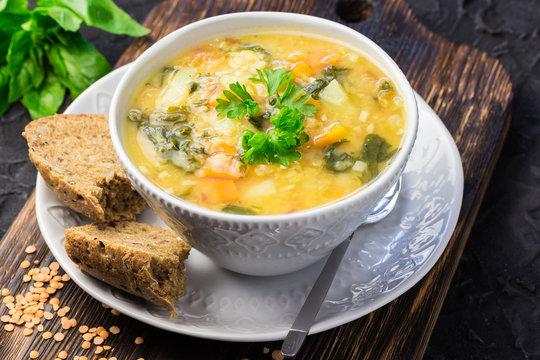 Golden lentil spinach soup on wooden dark background.
