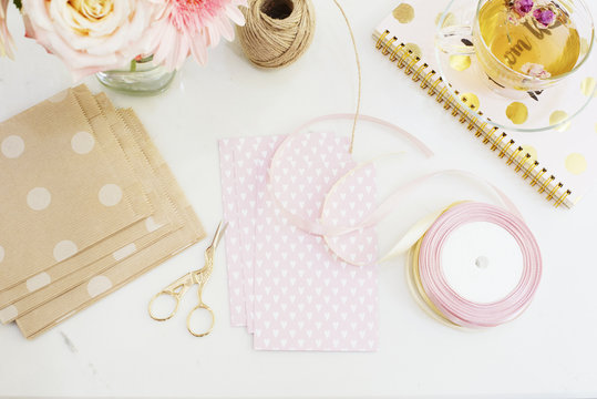 Handmade, craft concept. Materials for making string bracelets and handmade goods packaging - twine, ribbons. Freelance workspace in flat lay style with flowers, rose tea, notebooks