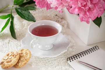 Red berry or fruit tea in teacup with peony