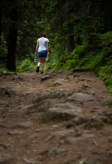 Hiker in mountain forest carries bottled water