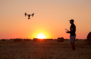 Poster Helicopter Man operating a professional drone at sunset
