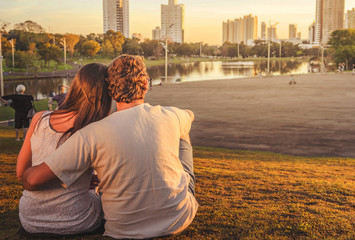 Couple in love seated on grass one next to other at park with a lake a nature around. Sunset with warm colors. Couple aligned to the left.
