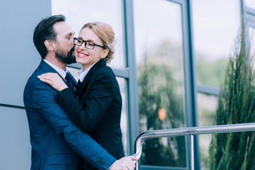 happy mature business people hugging and kissing while standing outside