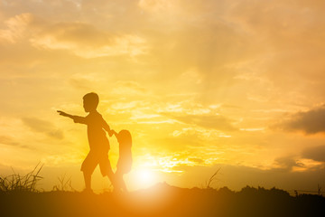 Silhouette of Boy and girl playing at sunset background, Happy children concept.