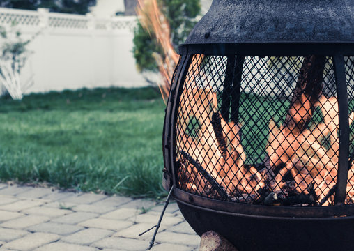 Outdoor fire pit with roaring fire. Chimera in backyard with strong fire and flames. Backyard with fire pit and white fence and lattice . Outdoor backyard paver with fire pit, green grass.