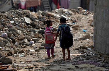 A boy and girl walk along rubble of a damaged house as they head to school in a slum in Karachi