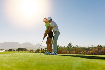 Personal trainer giving lesson on golf course