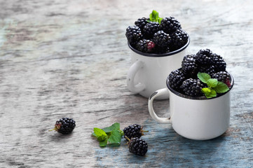 Fresh blackberries with mint leaves in a white cup on a rustic wooden background with copy space.